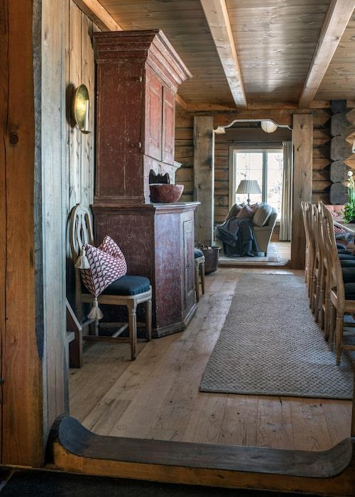 Från hallen stiger man in i matsalen som fått gustavianska stolar med tageltyg av John Boyd textiles. Det röda skåpet är vackert och ger bra förvaring. Innanför matsalen skymtar vardagsrummet. Ullmatta, Vandra rugs.