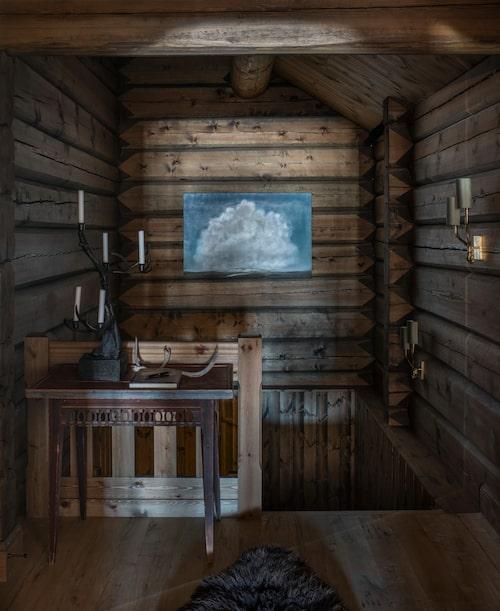Molntavlan av Ove Pihl går inte att missa på den annars mörka timmerväggen. Bordet och ljusstaken av gjutjärn är antika.