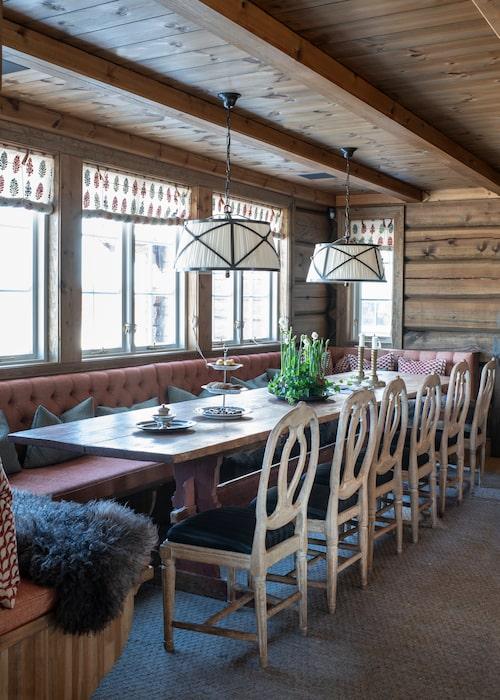 Ett långbord och en platsbyggd bänk ser till att det alltid finns plats för gäster kring bordet. Hissgardinerna är sydda av tyg från Vaughan och kuddarna i tyg från Le Manach/Pierre Frey. Ullmatta, Vandra rugs.