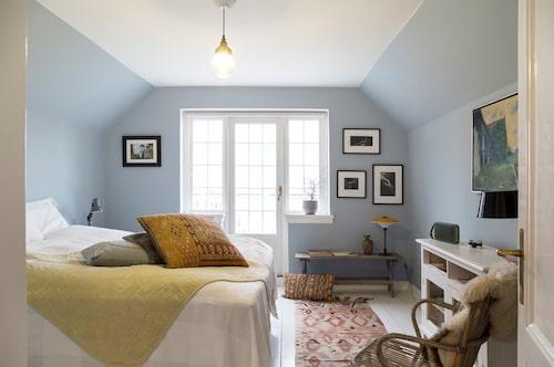 Föräldrasovrummet har utgång till en stor altan. Inredningen är en blandning av design och loppisfynd. Paret valde blå pastellton på väggarna för att bryta av mot husets många vita rum.