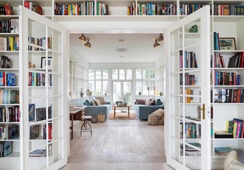 Den stora bokhyllan är platsbyggd runt dörröppningen mellan de två sällskapsrummen.