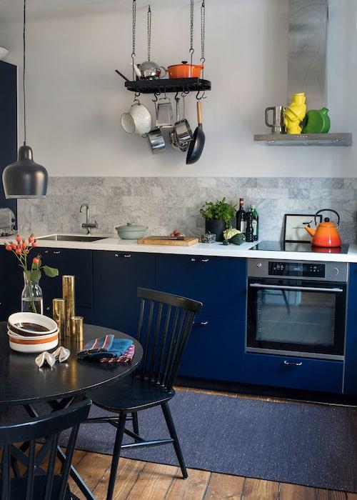Köksstommar, bänk i massiv akryl och vitvaror är från Ikea, och träluckorna från Järfälla kök. Stänkskydd av marmorkakel. Hängande grytförvaring, Crate & Barrels Ceiling pot rack, som pulverlackerats svart. Bord, NK, pinnstolarna hittade Chary i Vitabergsparken, tog hem och målade svarta. Taklampa i finsk 40-talsmodell, Artek. Rörstrandsskålar Amanda, salt-och pepparkvarn i form av fortune cookies i silver, present från Charys syster i Hongkong, linne, Himla by Sköna hem.