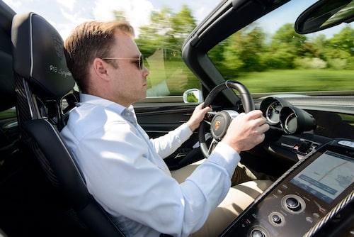 Han ser sammanbiten ut och frisyren klarar sig förbluffande bra i den öppna bilen. Mittkonsol à la uppförsbacke, en tydlig koppling till Carrera GT från 2004.