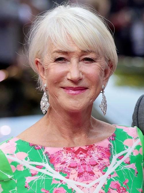 Skådespelerskan Helen Mirren, 74, lägger ena sidan av sin korta bob bakom örat.