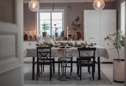 Dags för julfirande i det stora köket. Udda stolar, olika höga ljusstakar och färska tallkvistar blir charmigt inbjudande. Köksinredningen är från Ikea och har försetts med beslag från Specialbeslag.