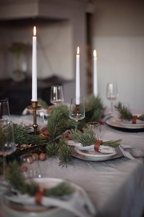 Skrynkligt linne, tallkvistar, nötter och tända stearinljus ger en lantligt rustik festdukning.