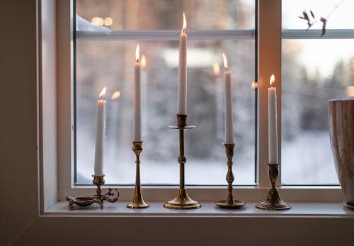 Fem ljushållare i mässing med levande ljus sprider värme och julstämning.