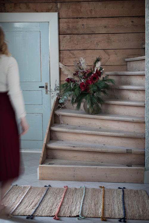I hallen och trappan tittar den råa timmerväggen fram, och bidrar till att ge huset gammaldags charm. Den härliga julbuketten kommer från butiken Blomman i Själevad.