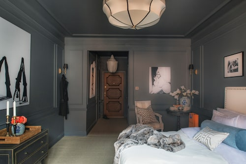 De svartvita fotona, från Yellow korner, och möbler och textilier i vitt skapar välbehövlig kontrast till den mörka väggoch takfärgen. Accenter i blått och orange lyser upp. Taklamporna och den gustavianska karmstolen är från Oscar & Clothilde, leopardmönstrad kudde, Day home.