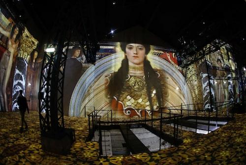 Besökare går runt och tittar på Gustav Klimt-utställningen på Atelier des Lumière i Paris.