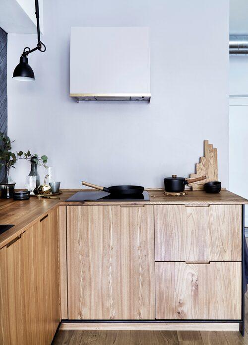Fläktkåpan med mässingskant (matchar blandarna) har Anitta designat i samarbete med Nilroy, kåpan målad i samma grå nyans som väggen. Spishäll, Witt, stekpanna, Eva Solo. I hörnet skålar från Raawi och Ditte Fischer, glaskanna, Housedoctor, mässingsäpple, Bloomingville.