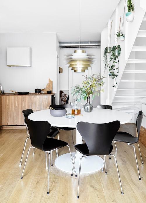 Hela familjen ryms runt matbordet i design av Ejvind A Johansson. Stolarna är Arne Jacobsens Sjuan för Fritz Hansen, mässingslampan kommer från Lysfabrikken.