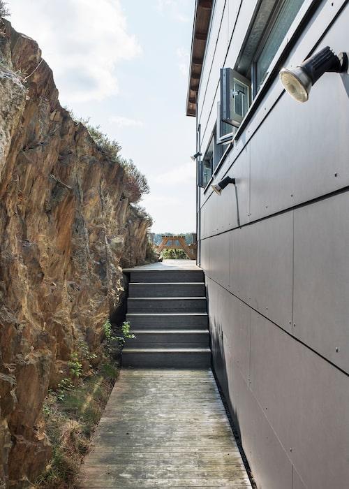 På baksidan mot berget är det lä. Det ser ut som eternitplattor på fasaden men är ett ofarligt keramiskt material. Trätrallen går runt hela huset och spotlights lyser upp på kvällen.