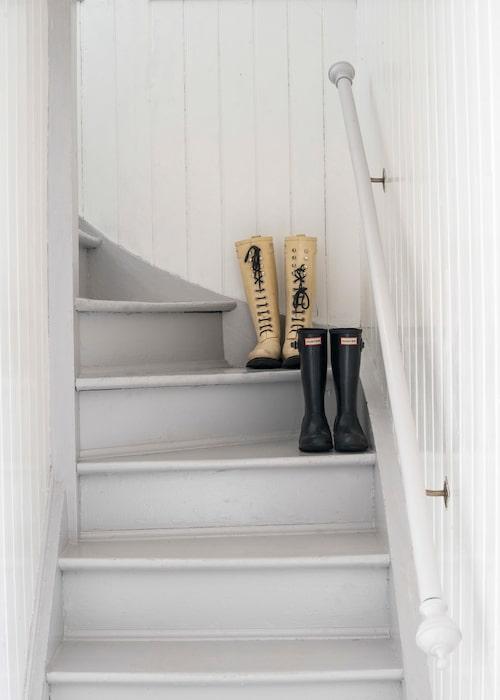 Vita väggar och ljusgrå trappsteg i trätrappan till övre plan.