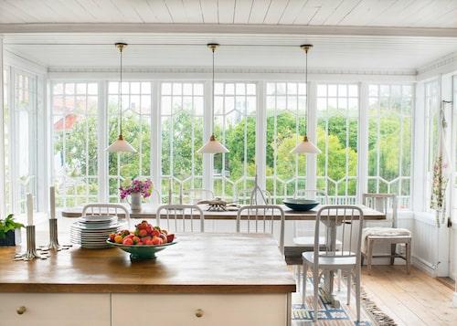 Köket har öppen planering och generöst ljusinsläpp från glasgalleriet. Bockbord från 1800-talet, matta av Märta Måås-Fjetterström, och över bordet skomakarlampor från Sekelskifte. I förgrunden ljusstakarna Flow av Sissi Westerberg för Svenskt tenn.