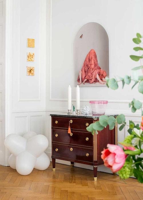 I ena hörnet i vardagsrummet, en spännande samling: Över den gustavianska byrån, fotot Octopus oracle av Lovisa Ringborg, samt tre små gula tavlor bestående av pressade blommor, av norska konstnärinnan Line Bergseth. På golvet prototyp av Tom Dixons lampa Jack.
