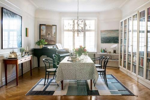 Modernt och klassiskt i vardagsrummet. Bord och sidobord av Anika Reuterswärd för Fogia. Thonetstolar, matta Cornici av Ami Katz för Vandra rugs. Över flygeln ett beställningsverk i olja av Ebba Heuman föreställande dottern i huset som dansar balett.