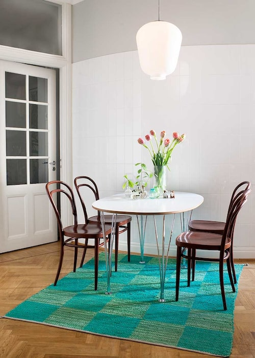Den rundade väggen i köket har klätts med stående kakel för att framhäva ljusets reflexer. Ett litet superellipsbord av Piet Hein för Bruno Mathsson, och Thonets kaféstolar utgör frukostplats. Mattan har Erika designat tillsammans med Vandra rugs.