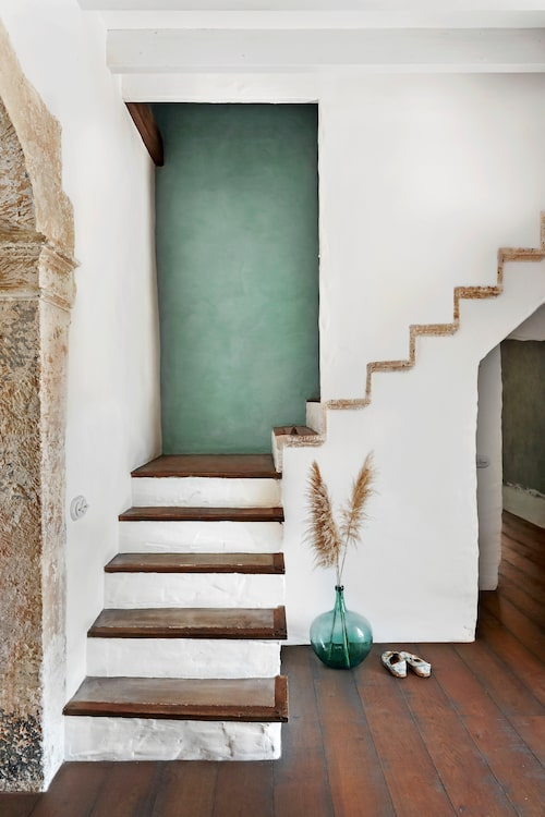 En av trapporna i huset som leder upp till övervåningen där sovrum och badrum ligger. Här skymtar vi den vackra gamla valvsöppningen som leder in till salongen.