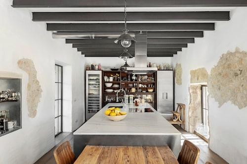 Köket ligger i en sidobyggnad i anslutning till huvudbyggnaden. Här finns en rejäl köksö och platsbyggd förvaring med trähyllor, kyl och vinkyl. Takets järnbalkar och fönstrens stålramar blir en spännande kontrast till de genuina stenväggarna och trägolvet.
