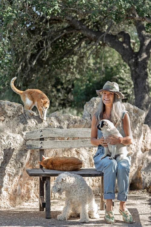 Annsofie med några av alla djuren som bor på gården. Den gamla träsoffan är tillverkad av trä från olivträd, den står utomhus året om och blir bara vackrare med åren.