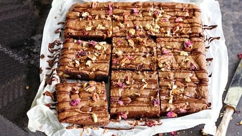 Garnera brownien med choklad, hackade pekannötter och rosenblad.