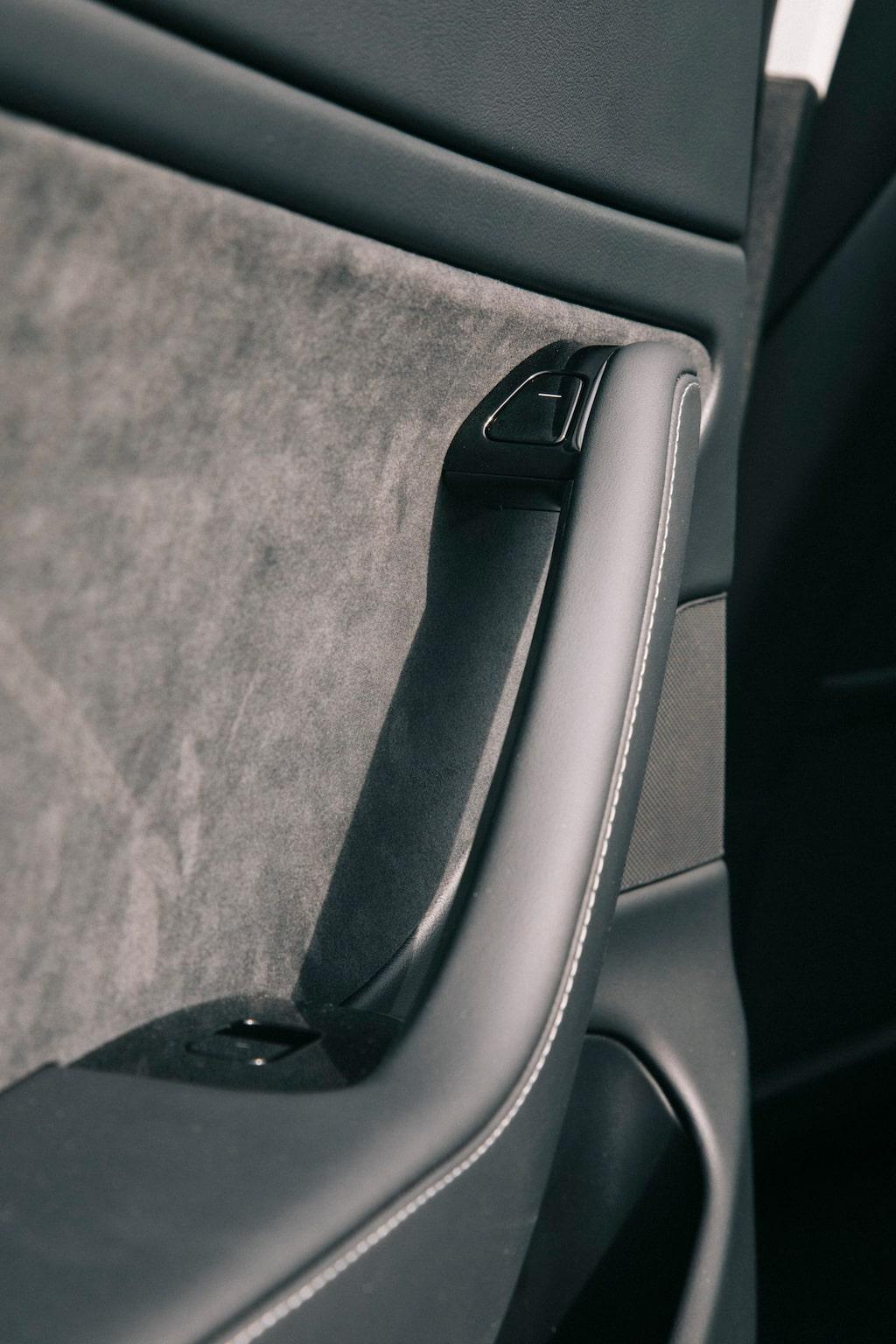 I Tesla Model 3 öppnar du dörren med knappen högst upp på dörrens armstöd.