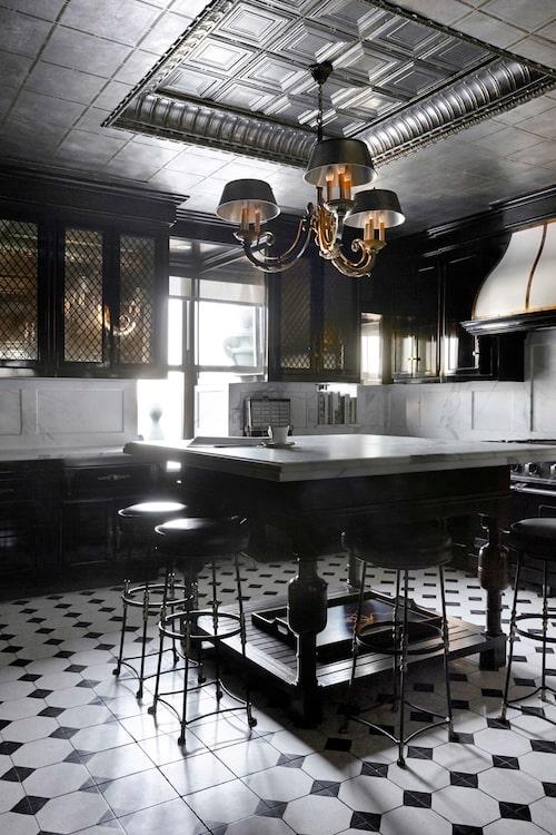 Köket är inspirerat av fransk bistro med svart inredning, mässingshandtag och marmor på arbetsbänkarna.