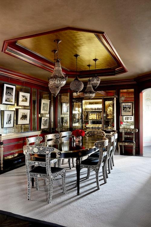 Inte bara en, utan ett helt kluster gamla ljuskronor hänger över det antika bordet. Runt om står skulpturala stolar med inläggningar av elfenben. En stor vitrin öppnar upp med dricksglas och objekt. På väggen syns Harry Bensons fotografier av dåtidens kändisar.
