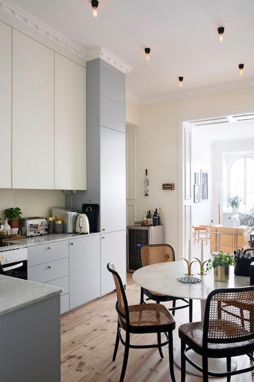 Köket ligger mitt i lägenheten, i det som förut var den inre hallen. Här är det verkligen hemmets hjärta, placerat precis bredvid vardagsrum och matsal. Thonetstolarna är fyndade på Blocket. Bord Tulip av Eero Saarinen.