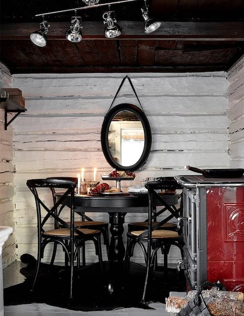 I köket har väggstockarna målats vita. Röd spis och matsalsmöbler i svart blir en fin kontrast.