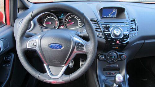 Ingenting förutom ST-loggan i rattens nederkant, röda siffror på växelspaken och aluminiumpedaler skiljer ut ST-versionen.