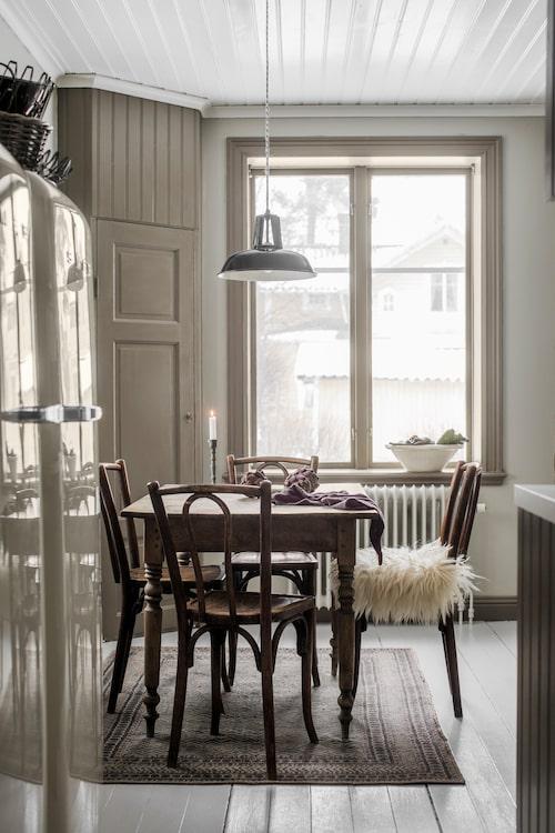Betraktelse från hallen in till köket. Det lilla hörnskafferiet har paret själva byggt och med en gammal dörr från vinden. Gräddvit kyl och frys från Smeg. Köksbordet och Thonetstolarna är vintage. Taklampa från Nordal.