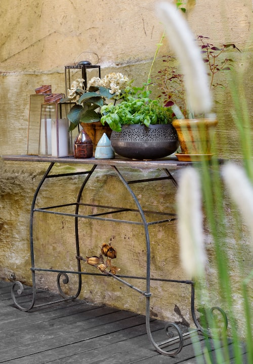 Trädgårdsbord med plats för krukor, örter och lyktor, bordet har Lena själv byggt ihop av ett metallunderrede och träskivor.