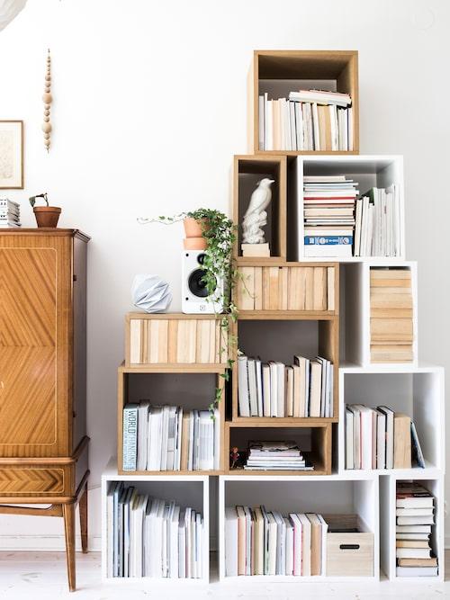 I vardagsrummet står en hemsnickrad bokhylla av olika stora kuber. Fågel i porslin från Artilleriet.