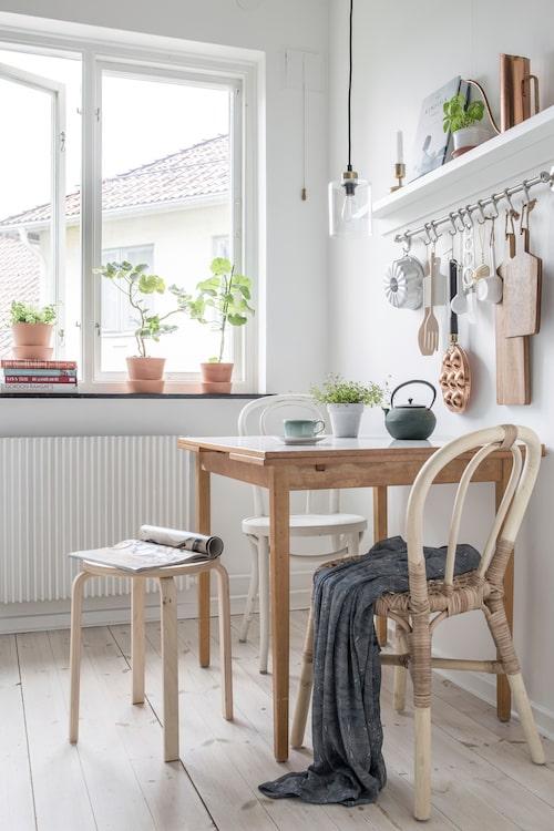 Lilla matplatsen. Blocketfyndat bord med klassiskt Virrvarrmönster. Pall och stol i naturträ, från Ikea, likaså den vita Öglanstolen. Lampa från Lagerhaus.