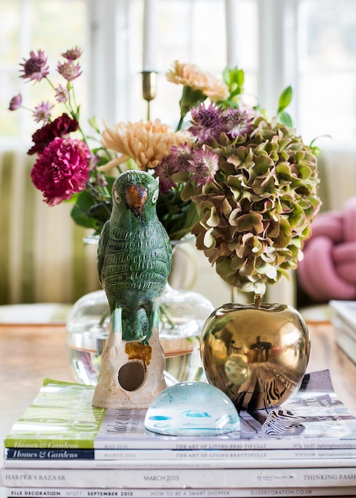 Installation på några glansiga månadsmagasin: Papegoja, guldäpple och brevpress från Slottsträdgården Ulriksdal.