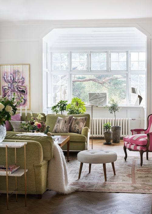 Mer konst: Keramikmunnen i fönstret är av Hertha Hillfon och målningen i rosa-lila-grönt är signerad Arman. Guldig skruvad bordslampa, Habitat, vit lampa i mässing 2468, Svenskt tenn. Mattan är en pakistansk ziegler (så kallas de handknutna mattor som tillverkades 1883–1930 Arakdistriktet i Iran, i regi av brittiska företaget Ziegler & Co).