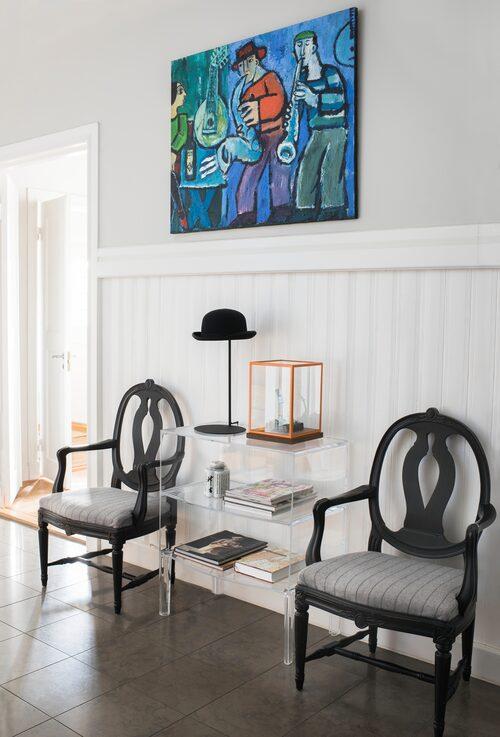 Plexiglasbord, Kartell, flankerat av gustavianska stolar. Hattlampa, R.o.o.m, glaskub, Asplund, med liten muranoglas-skulptur. Polska konstnären Krzysztof Kokoryn har gjort den svängiga oljemålningen. På golvet kalksten.