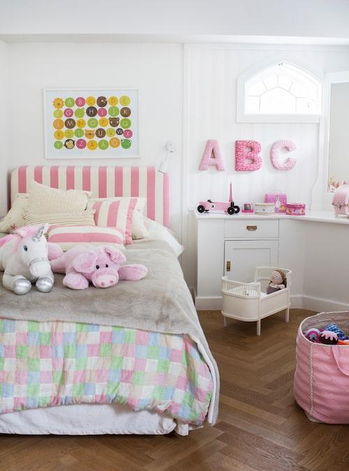 Här bor en liten tjej som också älskar rosa. Det lilla fönstret och den vita förvaringsmöbeln med spegel är en platsbyggd originallösning från 1906.
