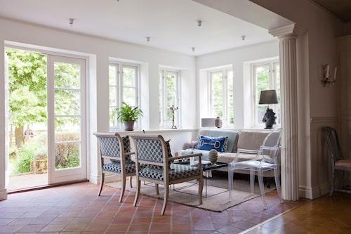 """Glasverandan var från början en utomhusveranda som Johans föräldrar lät bygga in i början av 1990-talet. Sitthörnan är möblerad med danska plåtbord, Philippe Starcks plaststol """"Ghost"""", en bekväm soffa samt två sengustavianska karmstolar."""