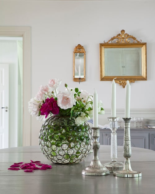 På bordet står en vas med snittblommor samt silverljusstakar. På väggen hänger en spegel från Johans föräldrar och spegellampetter från Annas mamma.