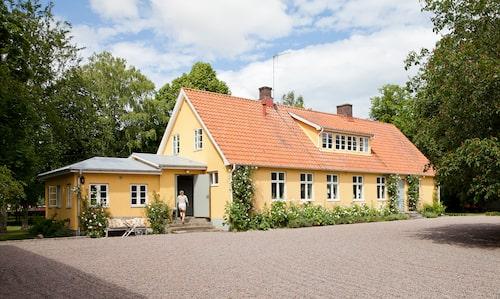 Sedan Johan och Anna flyttade till Axberga har deras behov av mer ytor ändrat mangårdsbyggnadens utseende något med en utbyggd groventré på ena gaveln.