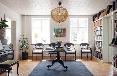 Bibliotekets hyllklädda vägg ger rummet en ombonad karaktär. Pelarbordet är ett Blocketfynd som Anna målat grått. Taklampan Heat från Northern i stickad mässing utgör en häftig kontrast till övriga möbler.