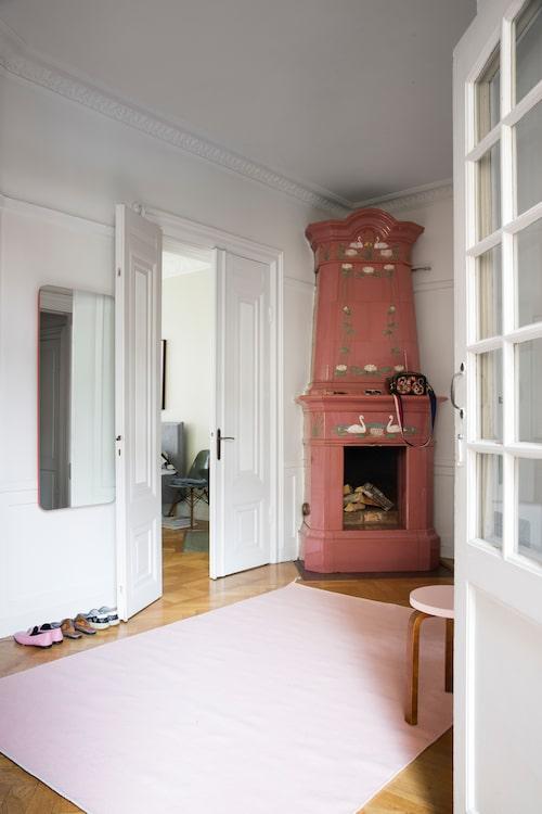 Mattan från Asplund matchar den charmigt svandekorerade kakelugnen i hallen. De vackra pardörrarna leder in till Marias sovrum.