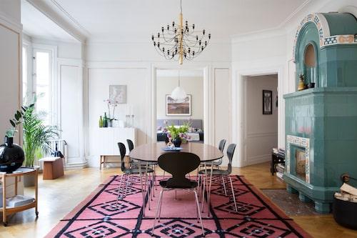 I vardagsrummets ljusa burspråk trivs växterna, och runt Superellipsbordet, på någon av Myranstolarna, trivs de tre familjemedlemmarna. I taket, Gino Sarfattis klassiska takkrona 2097, designad 1958. Matta med cool karaktär från Marias föräldrahem.