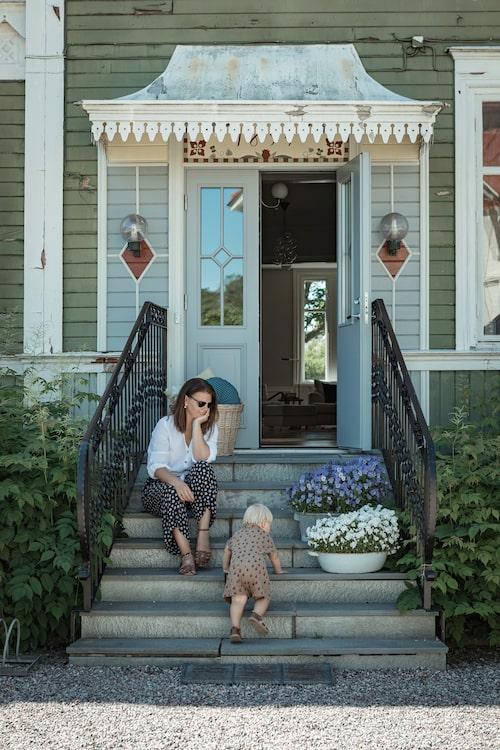 Anna och August vid Gröna husets vackra entré. Huset byggdes i början av förra seklet vilket syns på den vackra snickarglädjen.