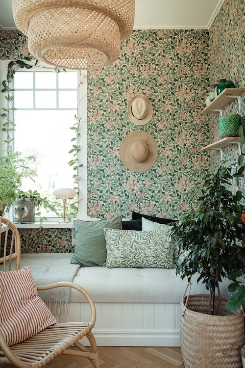 Den inglasade verandan är inredd med botaniska mönster och många gröna växter. Tapet, Honeysuckle, från William Morris. Korgstolarna är från Åhléns, rottingkorgen från Grandma's och taklampan från Ikea.