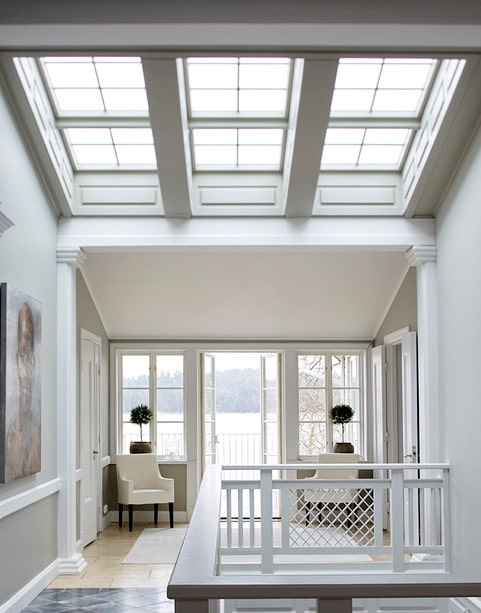 I den pampiga övre hallen behövs inga gardiner, himlen och havet blir en del av inredningen. Väggarna och de fina snickeridetaljerna, i form av pelare, lister och speglar, är målade i två olika grå nyanser.
