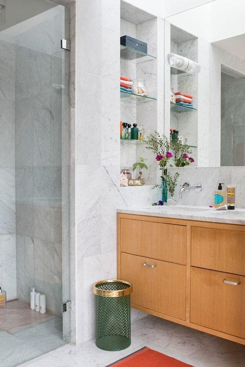 Kommoden är platsbyggd och har dubbla handfat och marmorskiva. Papperskorg i metall, Svenskt tenn. I den inbyggda hyllan med glasskivor står överst ett smyckeskrin i skinn från Palmgrens.